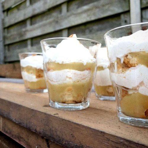 Vier glaasjes gevuld met laagjes beschuit, laagjes appelmoes en een laagje slagroom.